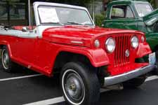 Front view shows narrow white walls and original wheel covers on a 1969 Jeepster Commando