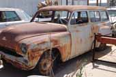 Very straight 2 door station wagon stored in vintage car junk yard