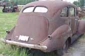 Nice 1940's 4-door sedan vintage project car in storage at old car junk yard