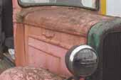 Original hood panels and headlamps on 1936 Chevy truck in vintage car wreckingyard