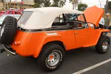 Striking orange and black paint job on a nicely up-graded vintage Willys Overland Jeepster