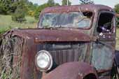 Rusty but original vintage Dodge truck, stored outside in grass field